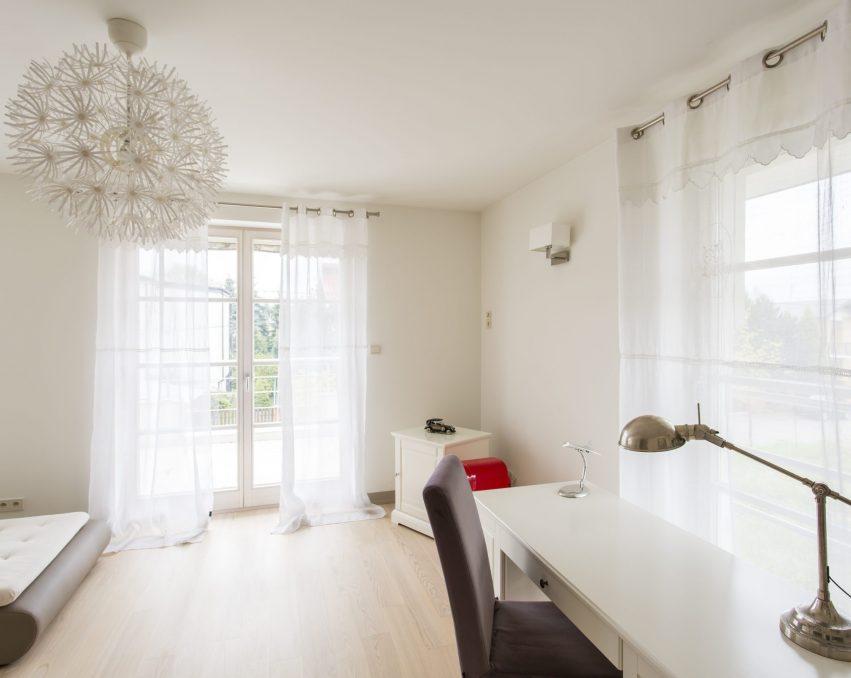 Modern, spacious interior with sofa, desk, big window and patio entrance